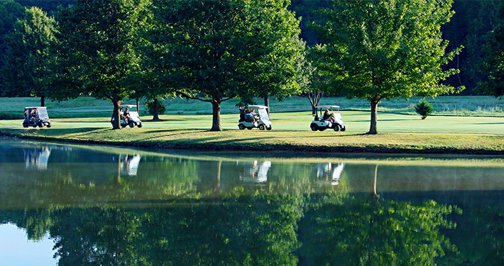 Golf carts on a path next to the water at Berksdale Golf Course