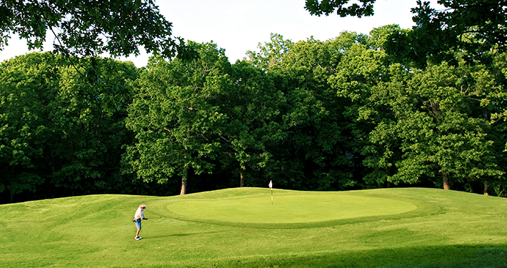 An landscape view of Brittany Golf Course with a golfer at a hole