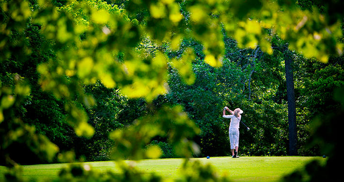 A woman swinging a golf club on a course surrounded by green trees