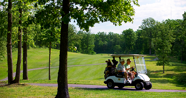 Two golfers riding in a golf cart at Dogwood Golf Course