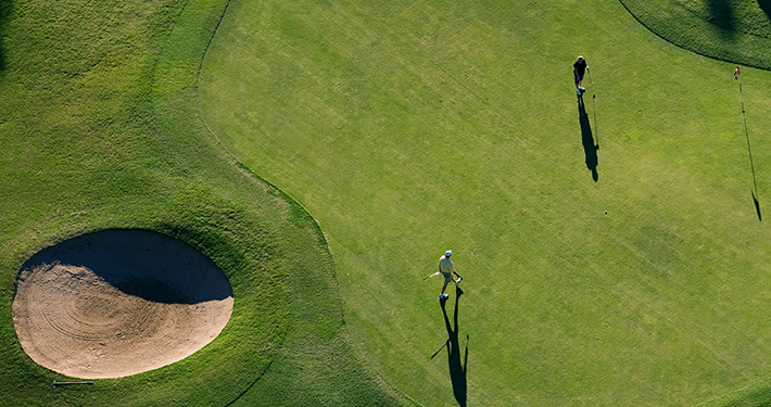 An overhead view of two people golfing at Highlands Golf Course