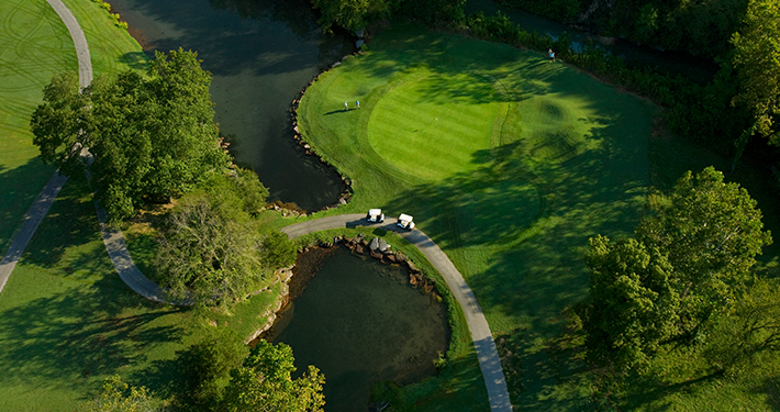 Two golf carts cruising a winding path at Scotsdale Golf Course