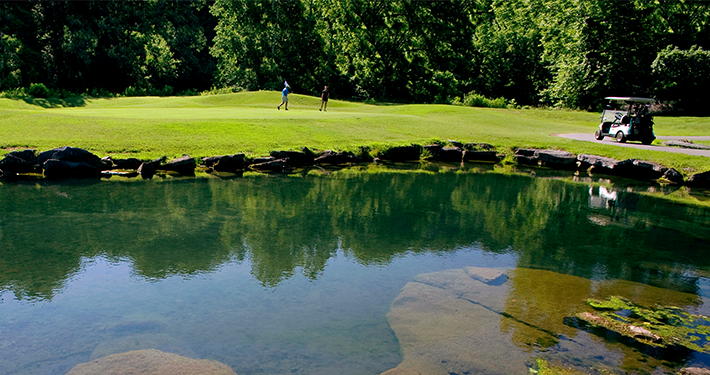 A pond at Scotsdale Golf Course with golfers in the distance