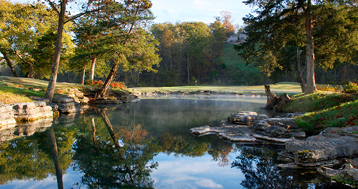 A beautiful scene of a pond and trees at Scotsdale Golf Course