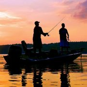 Two people fishing from a boat at sunset