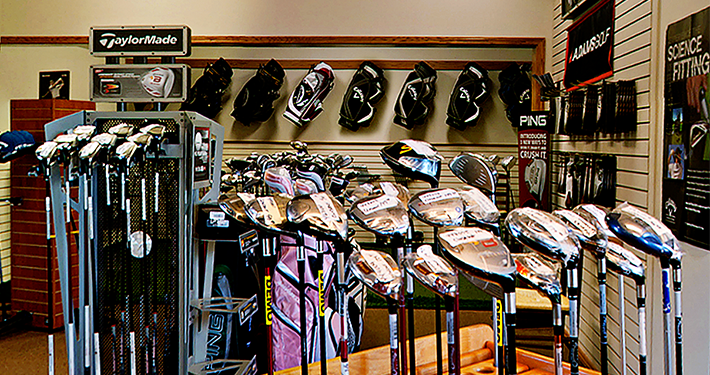 The interior of the shop at Golfers practicing drives at Tanyard Creek Practice Center featuring golf clubs and bags
