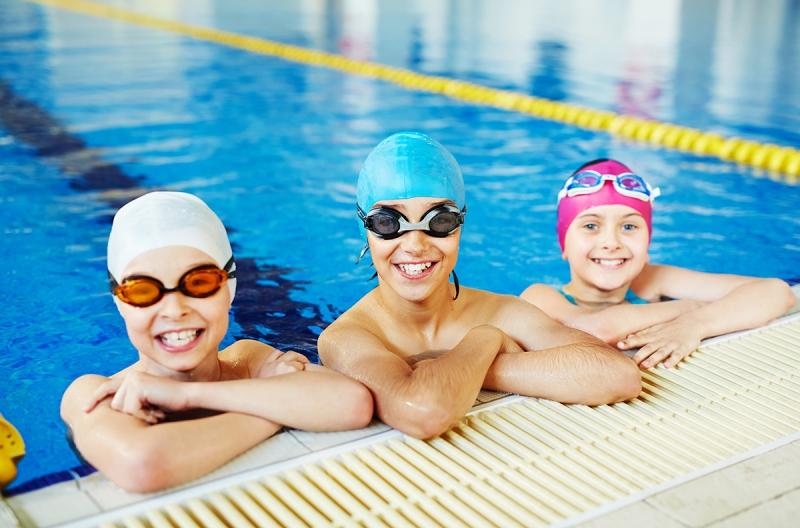 Children wearing googles and swimming caps in an indoor pool