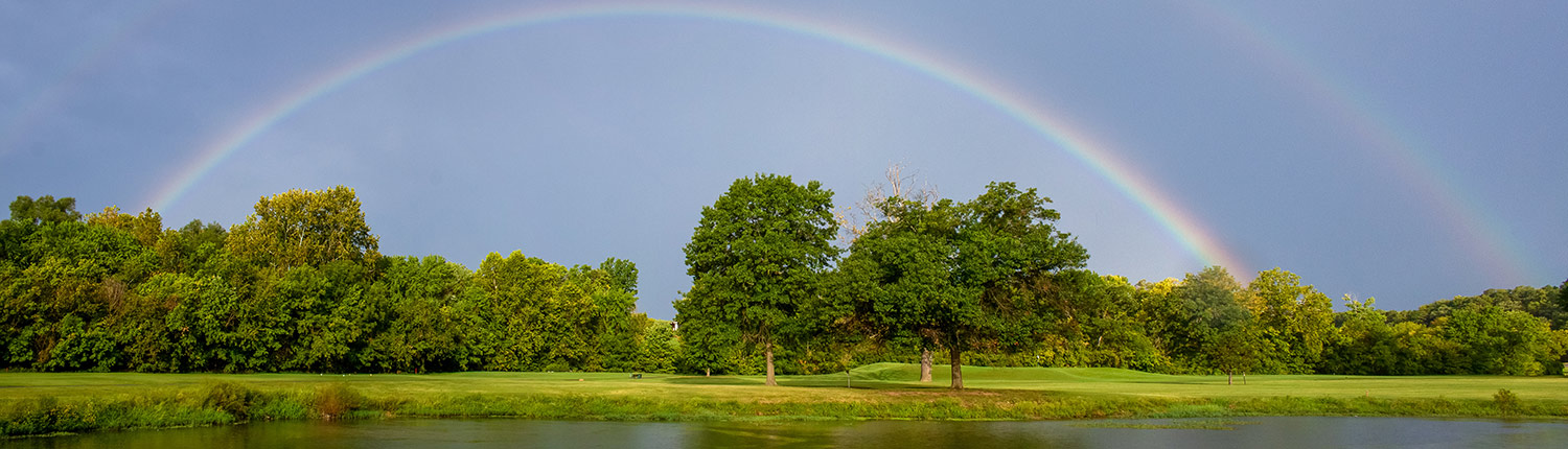 A double rainbow in a blue sky over a golf course and pond