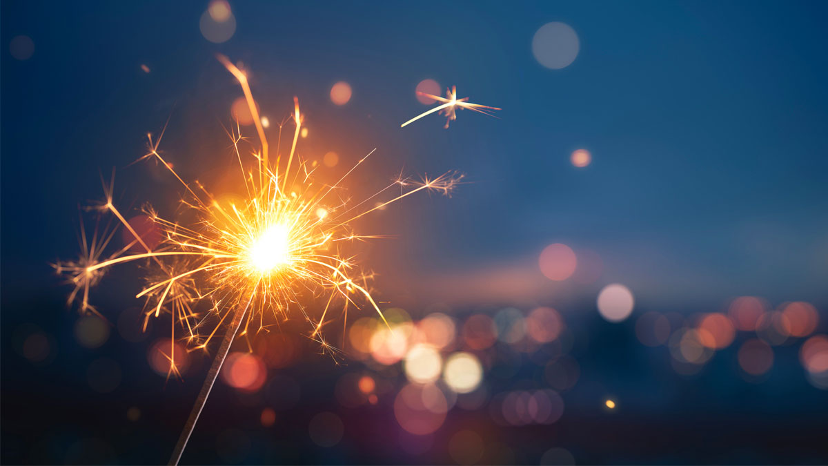 A lit sparkler glowing with a night backdrop.