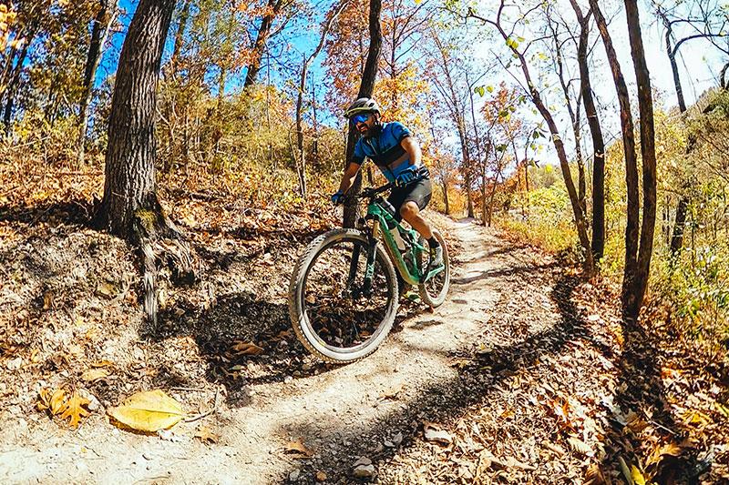 A mountain biker riding through the Little Sugar Trails.