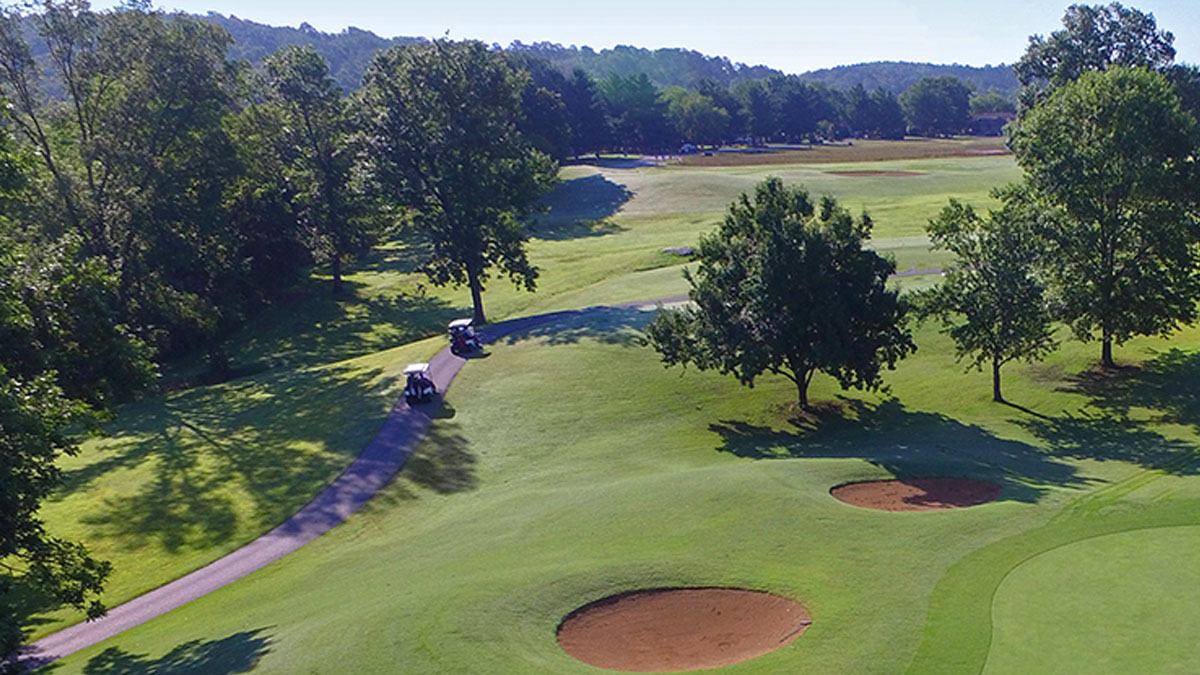 An overview of County Club Golf Course with two carts on a path.